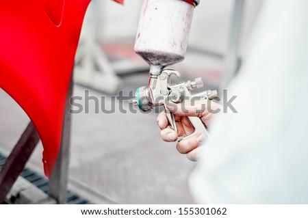 Close up of spray gun painting a car  - stock photo