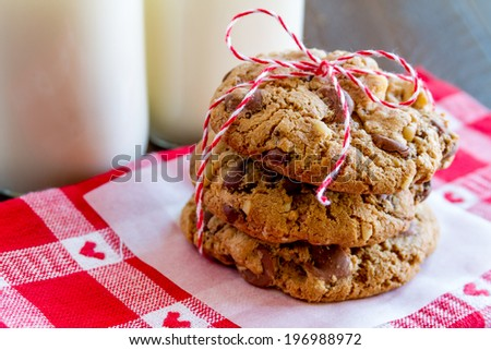 Close up of stack chocolate chip cookies tied with red bakers twine and a plate of cookies sitting on heart napkin - stock photo