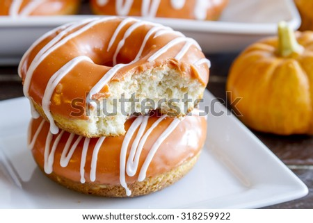 Close up of stack of homemade baked pumpkin donuts with orange pumpkin glaze with bite in top donut sitting on white square plate with small pumpkin in backgound - stock photo