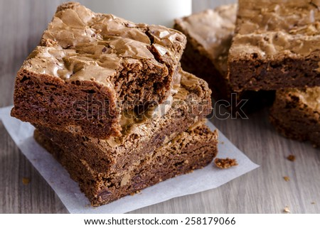 Close up of stack of homemade double chocolate chunk brownies sitting on wooden table - stock photo