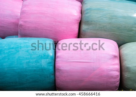 Close up of stack of pink, blue and green silage bags - stock photo