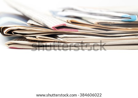 Close-up of stacked newspapers on white background. - stock photo