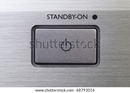 Close up of standby button on brushed metal background