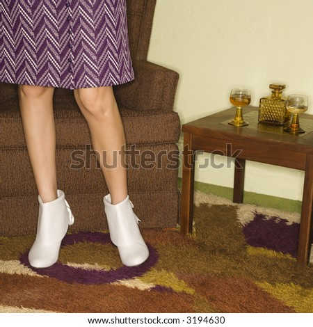 Close-up of standing Caucasian mid-adult female legs in vintage clothing. - stock photo