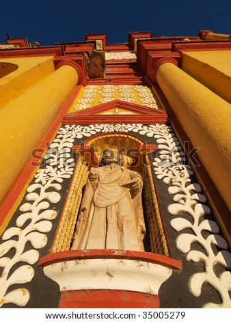 Close up of statue on old, brightly painted colonial church in the town center of San Cristobal de las Casas, Chiapas, Mexico. - stock photo