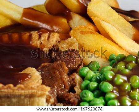 Close up of Steak Pie and chips with peas and gravy. A traditional bar meal. - stock photo