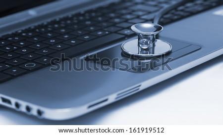 Close-up of stethoscope on laptop keyboard  - stock photo