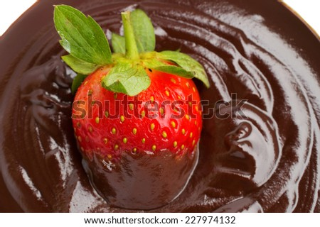close up of strawberries in chocolate syrup dessert on white background - stock photo