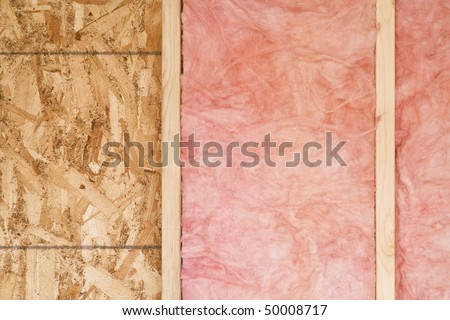 Close-up of strips of pink fiberglass insulation in a wall of a new building. Horizontal shot. - stock photo