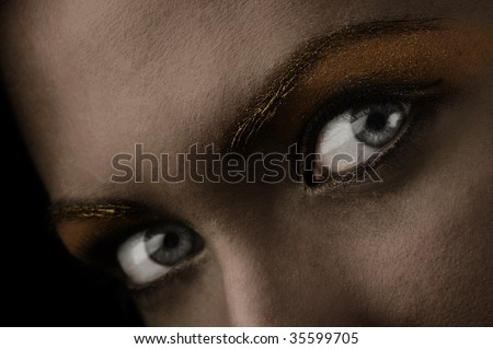 close up of stunning eyes in a dark desaturated shot - stock photo