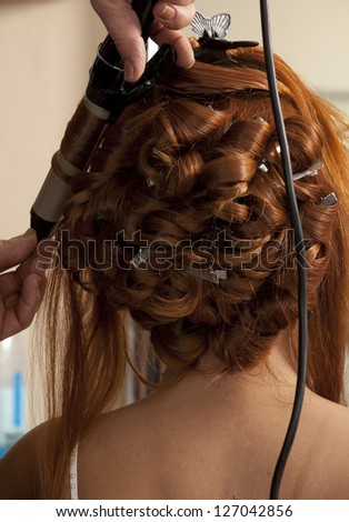 Close up of stylist's hand using curling iron for hair curls - stock photo
