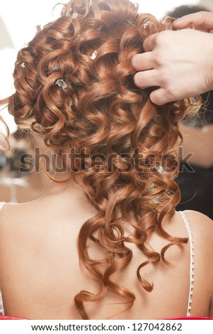 Close up of stylist's hand using curling iron for hair curls