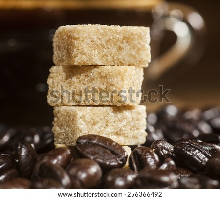 Close up of sugar cubes on coffee beans background and glass coffee cup.
