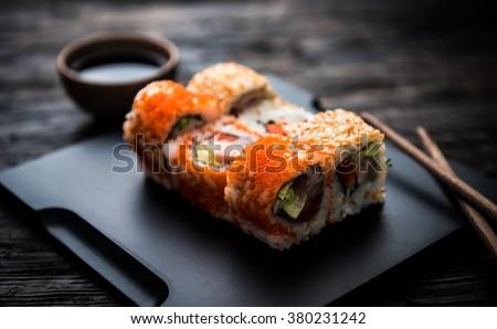 close up of sushi rolls on black tray - stock photo