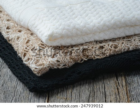 Close Up of Sweaters on Wooden Background - stock photo
