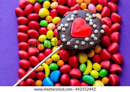 Close-up of sweet chocolate lollipop on colorful candies in arrangement on purple background - stock photo
