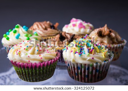 close up of sweet colorful cupcakes over gray background