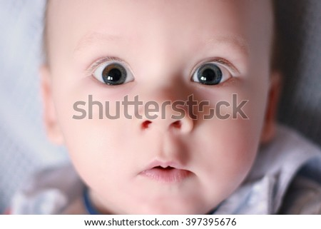 Close-up of sweet little baby face with a surprised look - stock photo