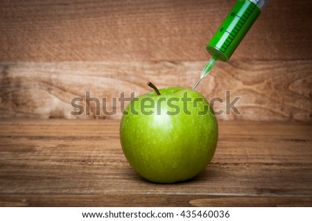 Close-up of syringe in green apple - stock photo