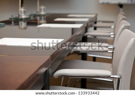 Close-up of table with armchairs in modern boardroom - stock photo