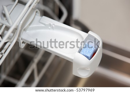 Close-up of tablet in dishwasher detergent box - stock photo