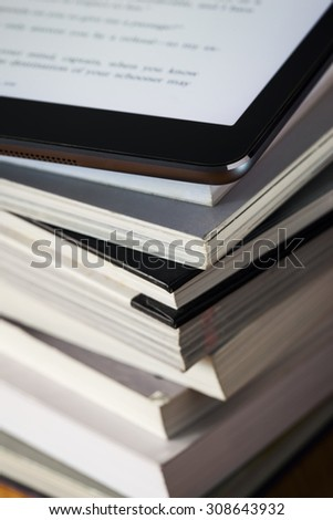 close up of tablet put on book stack - stock photo