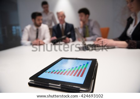 Close up of tablet touchpad computer with focus on business analytics and progress chart document. Business people group on meeting in background - stock photo
