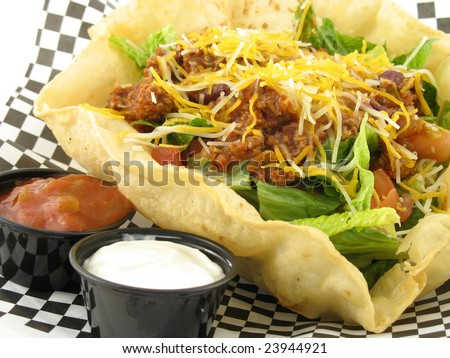 close up of taco salad with beef in a taco shell bowl with salsa and sour cream on side - stock photo