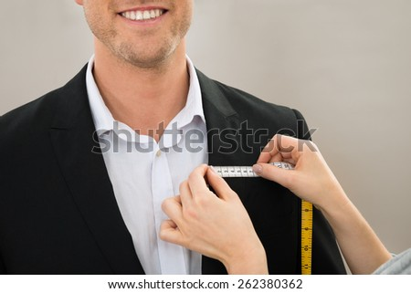 Close-up Of Tailor's Hand Taking Measurement Of Coat - stock photo