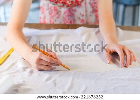 Close up of tailors hands drawing with pencil on fabrics - stock photo