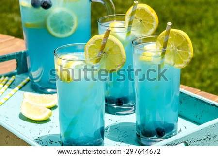 Close up of 3 tall glasses and pitcher filled with blueberry lemonade with fresh lemons and blueberries and yellow swirled straws sitting in blue drink tray - stock photo