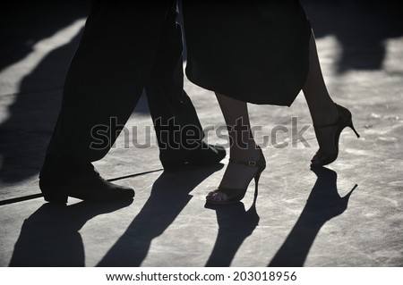 close-up of Tango dancers'?? foot step on pebble in silhouette - stock photo