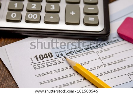 Close up of tax form 1040 with pencil, pink eraser and calculator