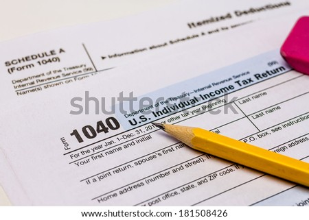 Close up of tax form 1040 with Schedule A and pencil