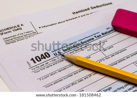 Close up of tax form 1040 with Schedule A. pencil and pink eraser