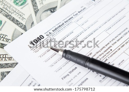 Close up of tax forms with dollar bills and pen - stock photo