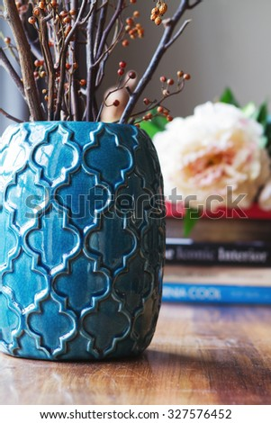 Close up of teal moroccan vase with sticks and background decor in home interior - stock photo