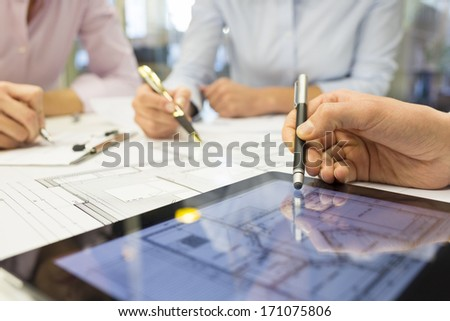 Close-up of Team architects working on construction project in office - stock photo