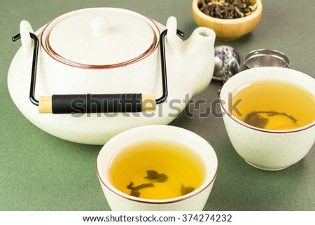 Close up of teapot and two cups with green tea on a green background.