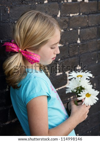 Close up of teen holding flowers by brick wall - stock photo