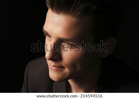 Close up of teenager boy against black background