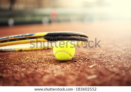 close-up of tennis ball and racket on clay court, summer day at tennis - stock photo