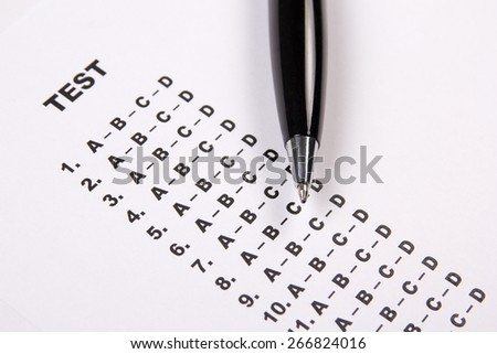 close up of test score sheet with answers and metal pen - stock photo