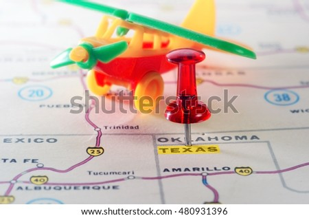 Close up of  Texas USA map with red pin and airplane  toy - Travel concept