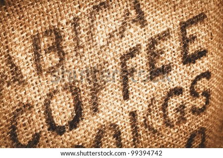 Close up of textured woven hessian fabric with the word Coffee stamped on it in a coffee background concept - stock photo