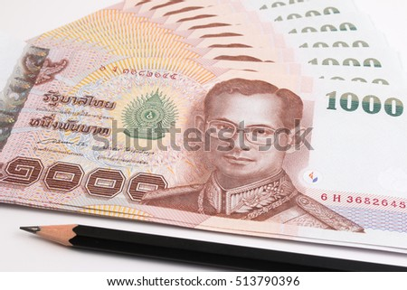 Close up of Thai banknote with black pencil, Thai bath banknote with the image of Thai King Bhumibol Adulyadej. Thai banknote of 1000 Thai baht. Thai currency banknote concepts.