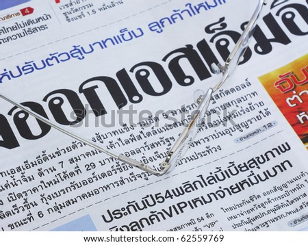 Close-up of Thai language newspaper and a pair of glasses. Shallow depth of field with focus on the nearest text and the glasses.