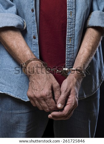 Close up of the arms of a mature man with handcuffs - stock photo
