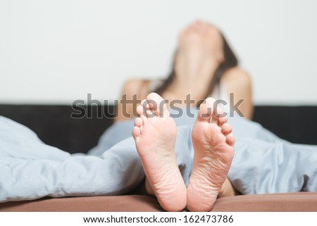 Close up of the cute crinkled soles of female feet belonging to a smiling playful woman relaxing in her bed with focus to the feet