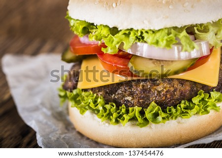 Close up of the delicious cheeseburger with a juicy beef, cheese, fresh lettuce, onion, pickle and tomato on a sesame seed bun photographed on a baking paper on a wooden table - stock photo